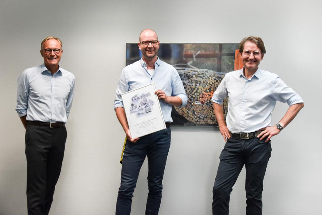 Drei Männer stehen vor einer Wand