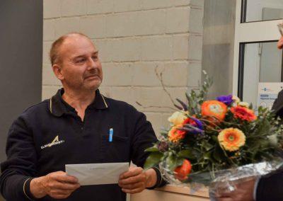 Mann vor Wand mit Blumenstrauß