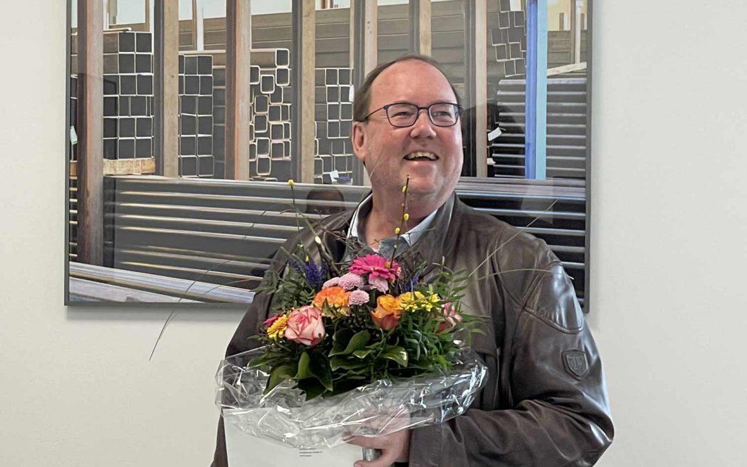 Mann mit Blumenstrauß in der Hand vor Bild