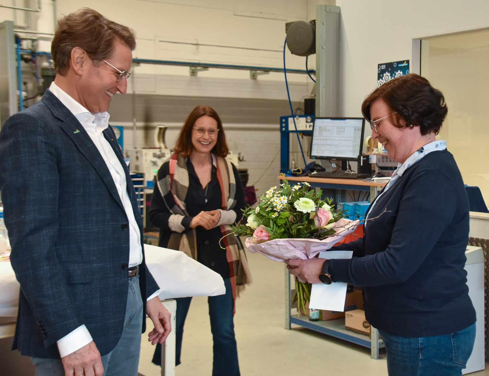 Zwei Frauen und ein Mann in einer Werkstatt. Mann gibt einer Frau einen Blumenstrauß. Alle lachen.