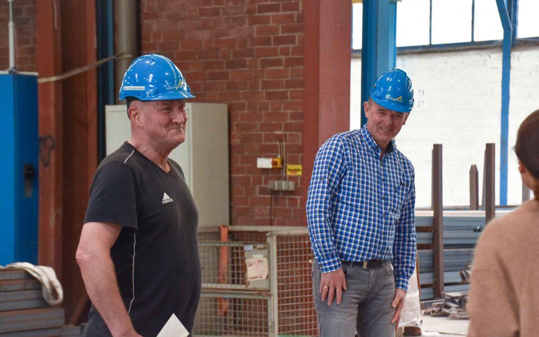 Zwei Männer lachen in Stahlhalle und tragen einen Helm.
