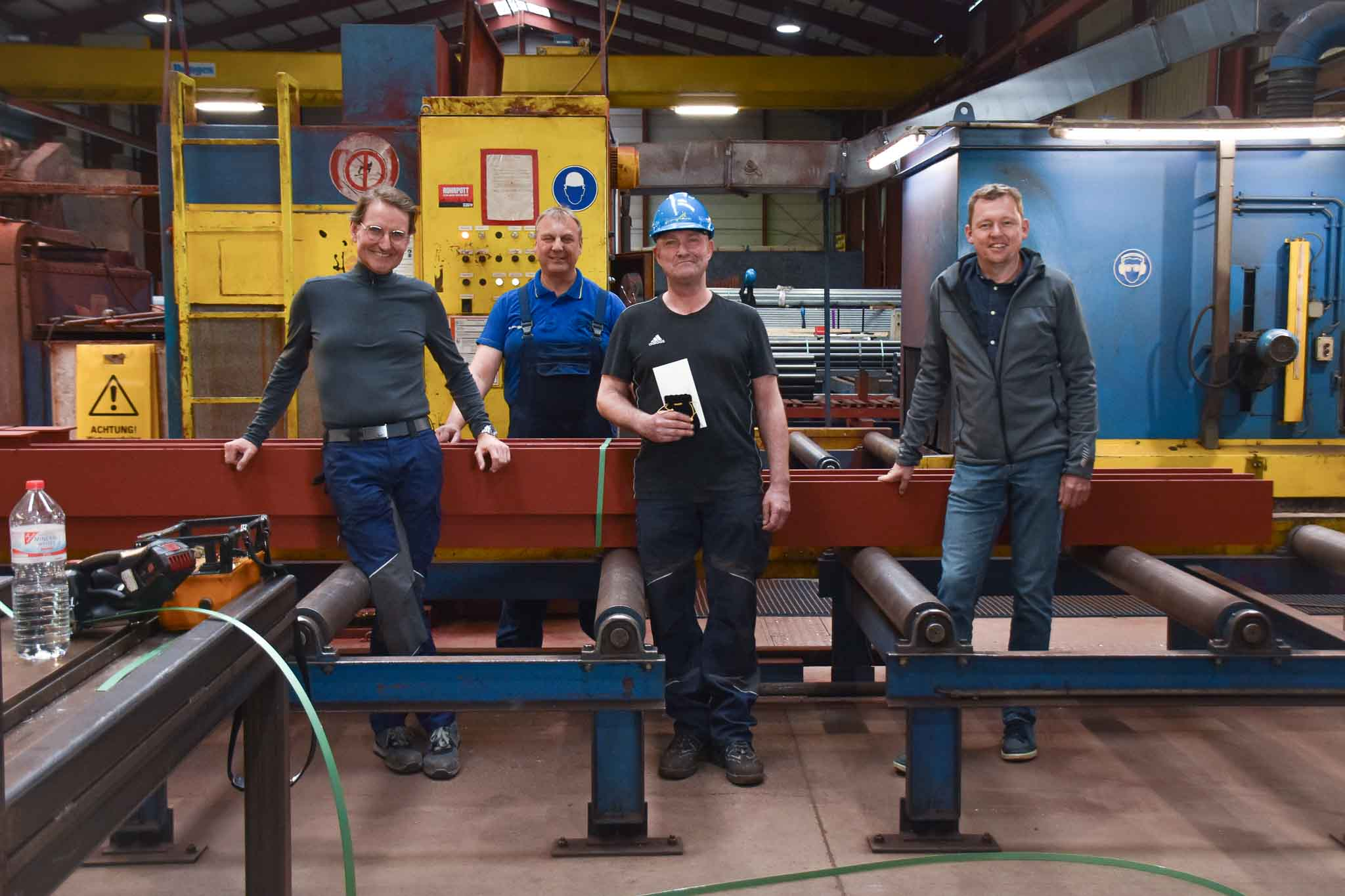 Männer stehen in Stahlhalle. Hinter Männern ist eine Stahlsäge.