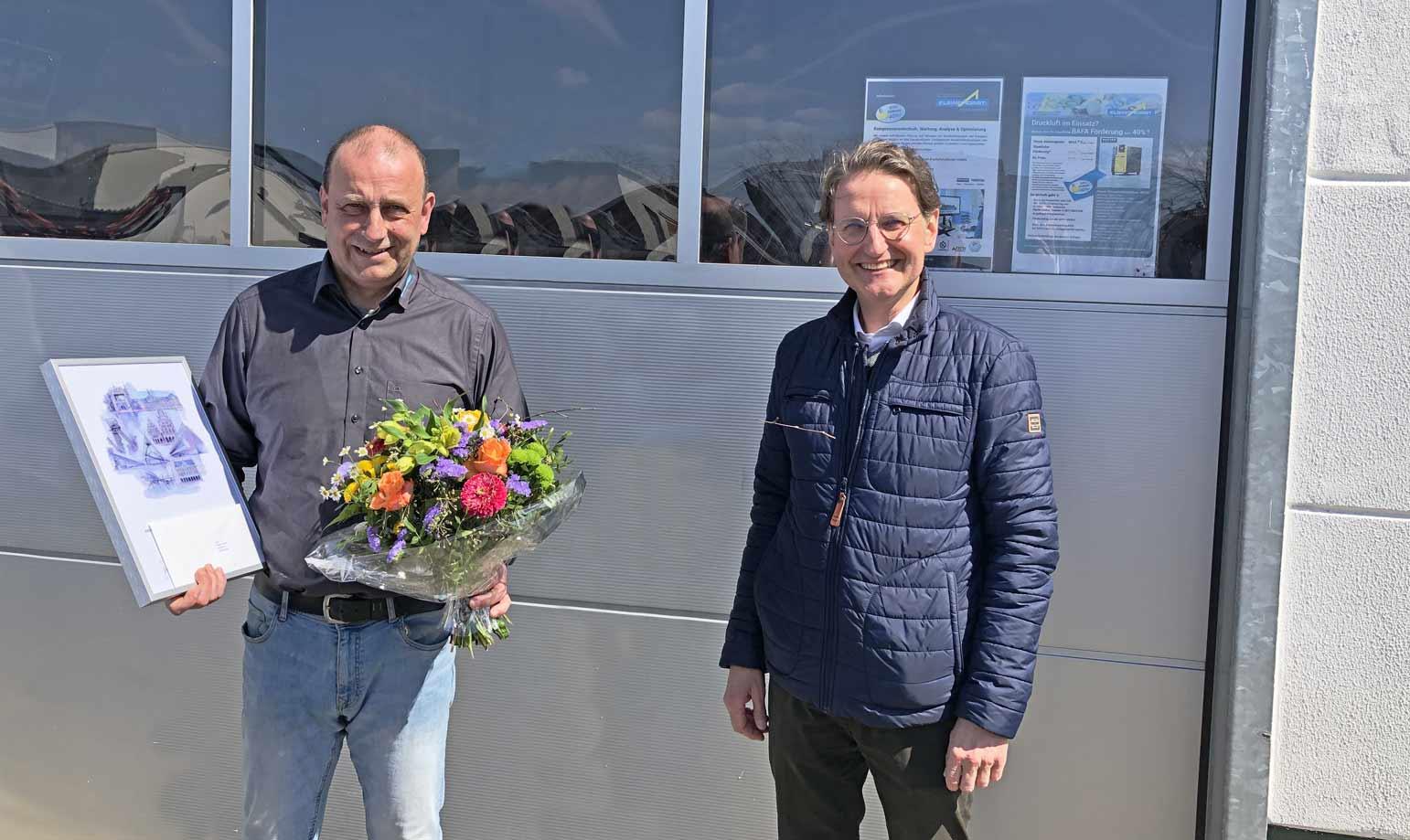 Zwei iMänner stehen vor Garagentor. Ein Mann hält Briefumschlag, Blumen und Bild. Beide lachen.