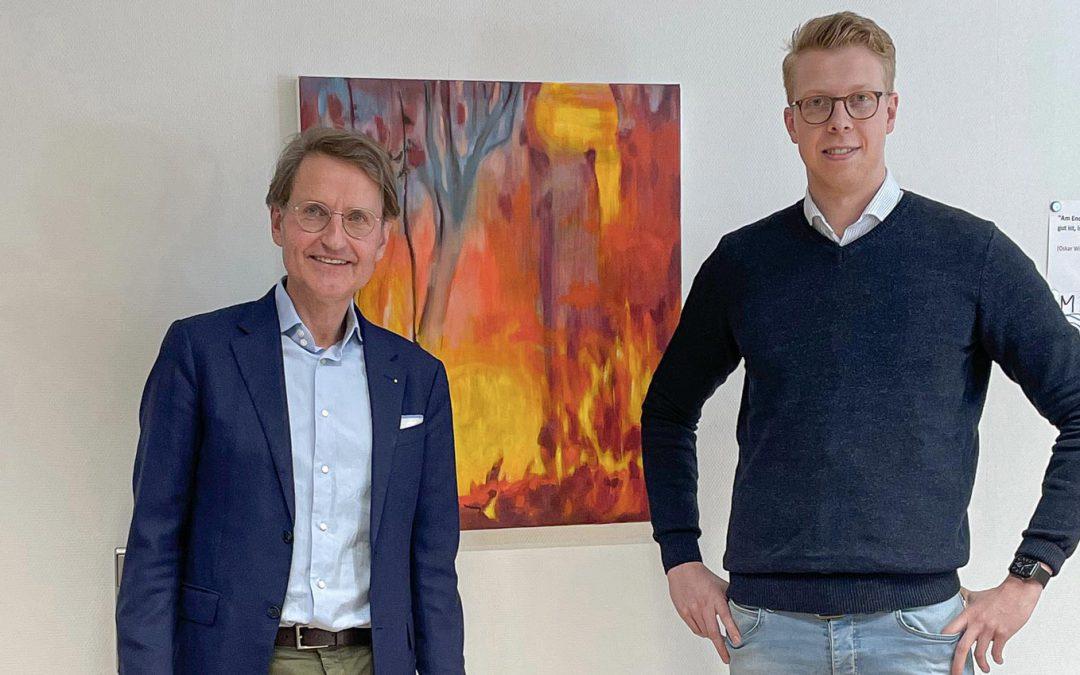 Zwei Männer stehen vor einer Wand. An der Wand hängt ein orange-rotes Bild. Beide tragen eine Brille und legere Kleidung.