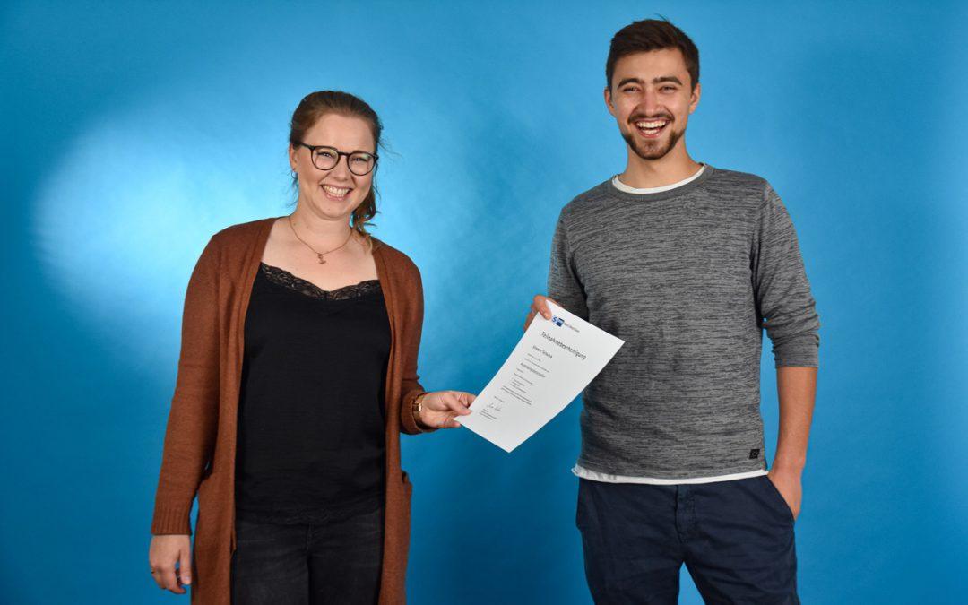 Junger Mann und junge Frau stehen vor einer blauen Wand. Sie lachen und halten gemeinsam ein Zertifikat in der Hand.