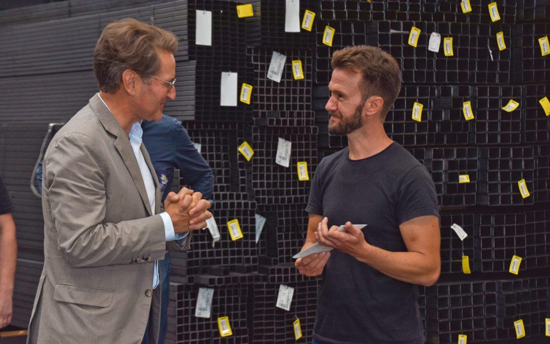 Zwei Männer unterhalten sich. Sie stehen in einer Stahl-Halle.