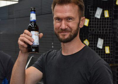 Mann steht in Stahlhalle. Er lacht und hält ein alkoholfreies Bier in der Hand.