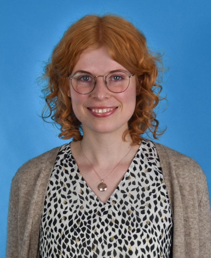 Frau steht vor blauer Wand. Sie hat orangene Haare und lächelt. Sie trägt eine gemusterte Bluse und eine Jacke.