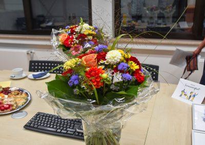 Blumen auf einem Tisch. Daneben sind Kuchen und Urkunden.