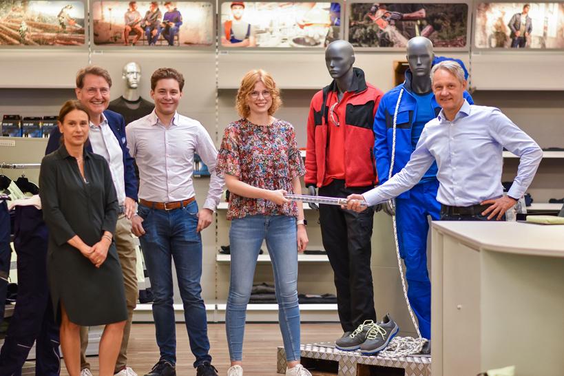 In einem Geschäft stehen 4 Personen nebeneinander und lachen in die Kamera.