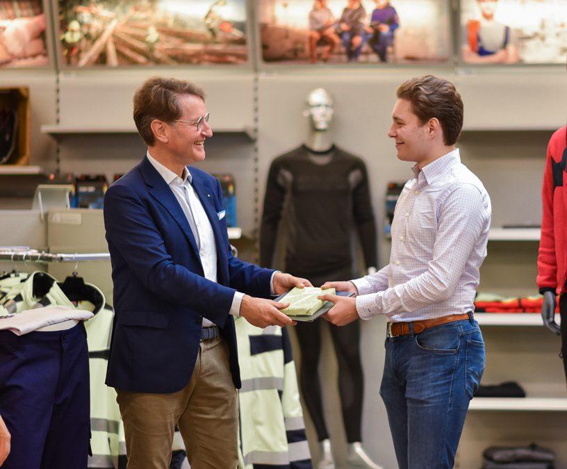 Zwei ;Männer stehen in einem Geschäft. Der rechte Mann schenkt dem linken Mann ein Geschenk. IM Hintergrund ist Arbeitsschutzkleidung zu sehen.